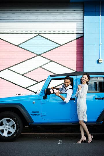 ブルーのラングラーを運転する新郎とその横に立っている新婦
