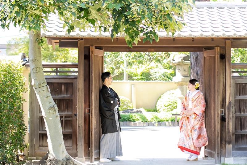 肥後細川庭園の門の前で向き合う二人