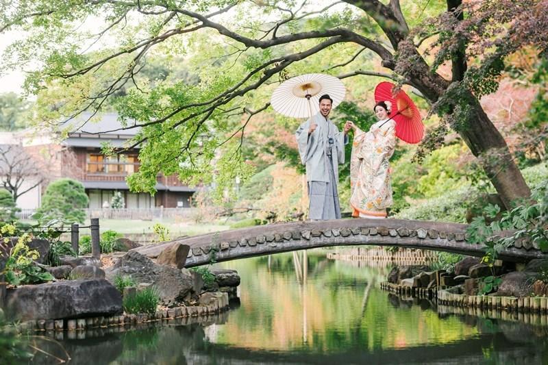 肥後細川庭園の人気スポットの橋の上で和傘を持って撮影