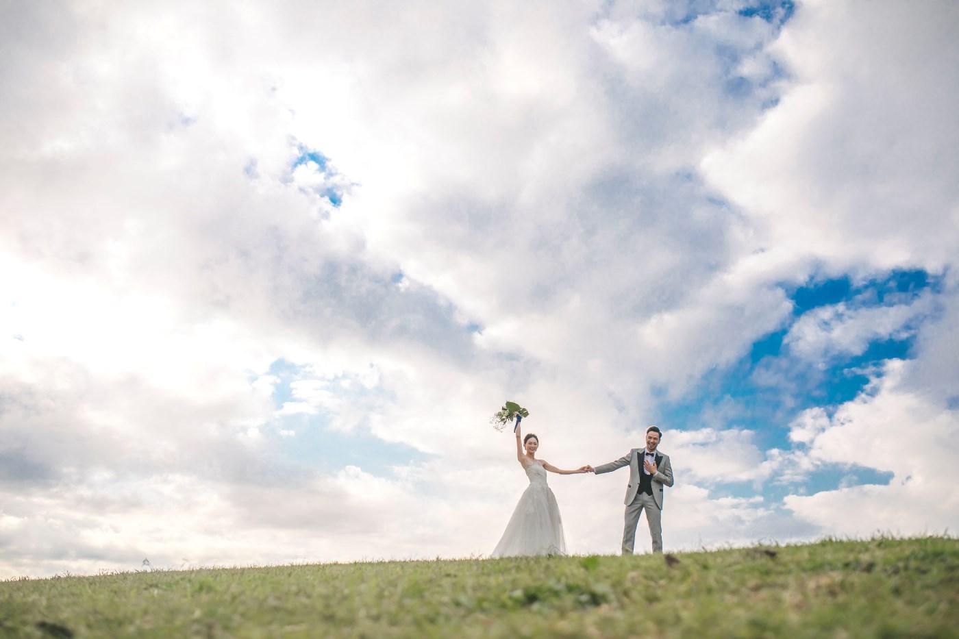 葛西臨海公園の丘の上で両手を挙げる新郎新婦