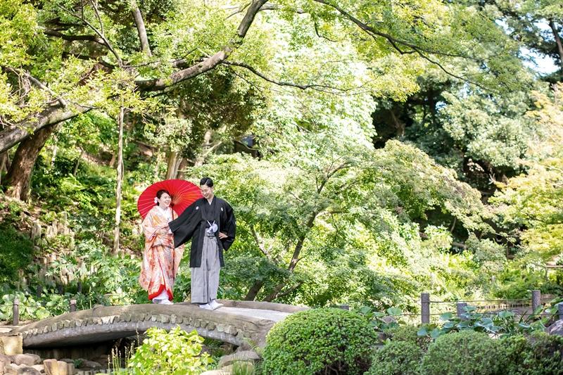 肥後細川庭園の橋で手を繋いで橋を渡るふたり
